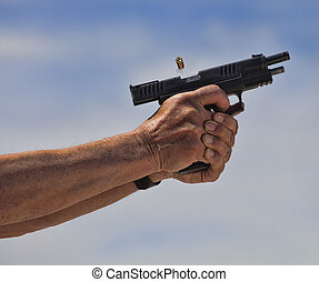 Shell and smoke leaving a handgun just after being shot