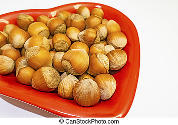 shelled hazelnuts on a red plate with heart figures