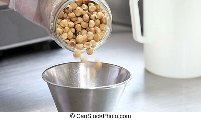 shelled hazelnuts poured from jar - shelled hazelnuts poured...