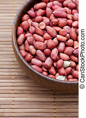 Shelled red peanuts in a wooden bowl