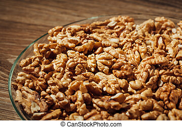 shelled walnuts on a plate, wooden background