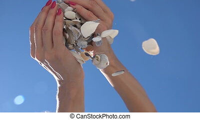 Shells fall from hands. Slow motion - Shells fall from...