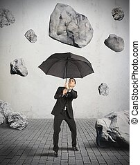 Shelter from the storm of crisis - Businessman shelters from...