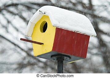 Shelter in snowstorm - Colorful birdfeeder in heavy...