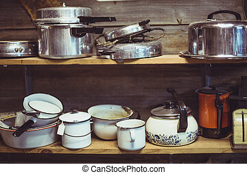 wooden shelves in thrift store cluttered with old pots and pans