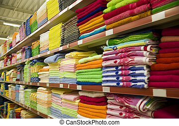 shelves of shop with varicoloured towels and fabric