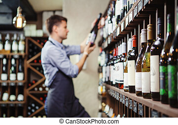 Shelves with elite wine and defocused thoughtful young sommelier