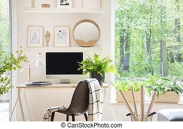 Shelves with illustrations above a wooden desk with computer...