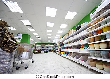 Shelves with variety of accessories for home flowers inside large supermarket