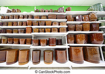 Shelves with variety of brown clay flowerpot inside large supermarket