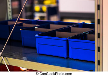 Shelving racks with empty blue boxes on a large modern warehouse