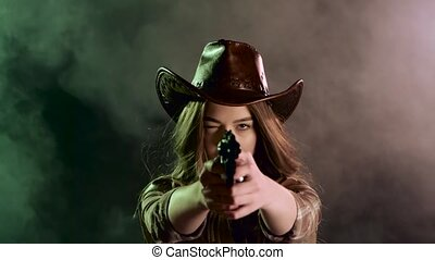 Sheriff girl holds a revolver in her hands and aiming at the...