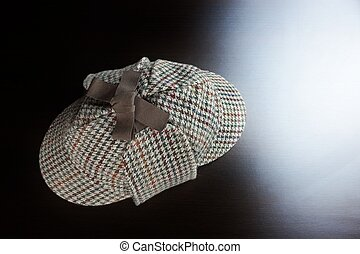 Sherlock  Holmes Deerstalker Hat On The Black Wooden Table