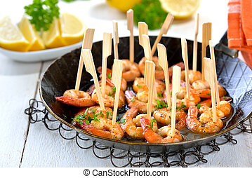 Spanish tapas - fried spicy prawns with olive oil, Sherry and garlic, served in an iron frying pan