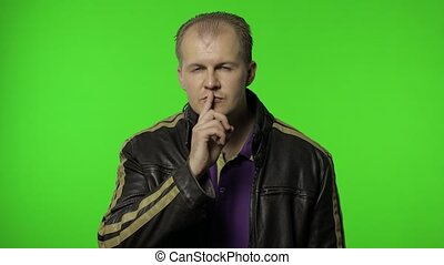 Shh, don't tell secret. Rocker man in brown leather jacket putting finger on lips making silence gesture, looking around with conspiracy, asking to keep mystery. Guy biker on chroma key background