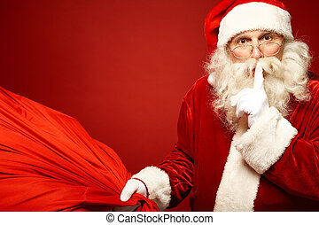 Shhh - Portrait of Santa Claus with huge red sack keeping...