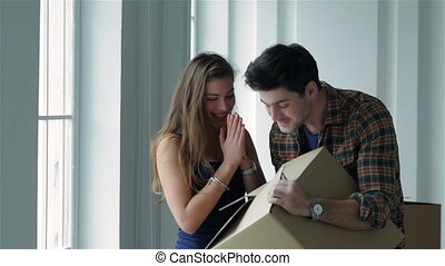 Shifting to new life. Couple in love moving and keep a box in his hands and looking inside box while a young and beautiful couple in love sitting on the couch in an empty apartment among boxes