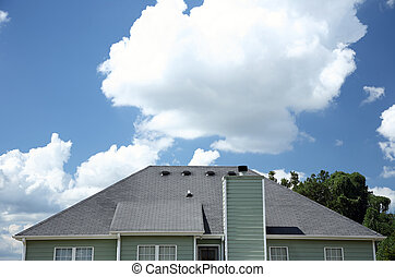 Shingled roof of a home - A rear view of a gray shingled...