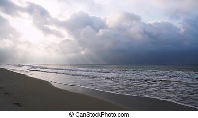 Loop features a sandy beach with crashing waves and sunbeams penetrating clouds above.