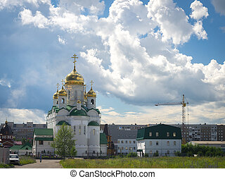 Shining golden domes of a Russian Orthodox Church in Barnaul with dramatic clouds on blue sky in summer afternoon