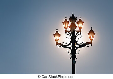 Shining lamps on blue sky with sun