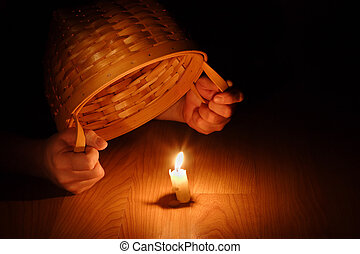 Hands holding a basket over a burning candle