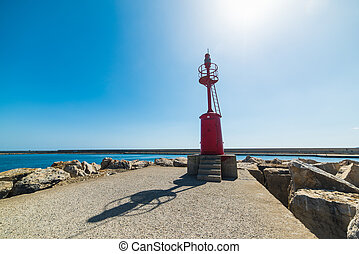 shining sun over a red lighthouse in Alghero