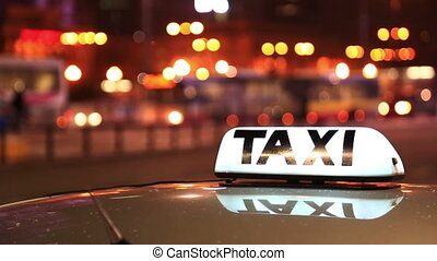Shining Taxi inscription against passing cars on night street of big city