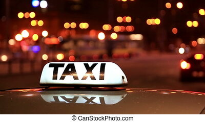Shining Taxi inscription against the passing cars on the night street of the big city