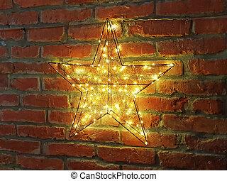 Shining yellow star on a brick wall