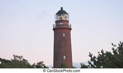 Shinning old lighthouse above pine forest before sunset....