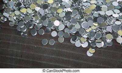 Shiny aluminium round billets fall from conveyor belt...