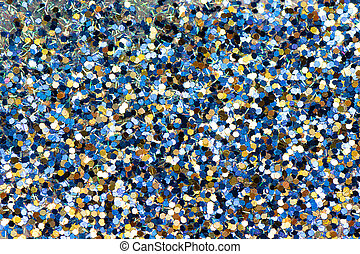 Shiny background with yellow and blue glitter close up.