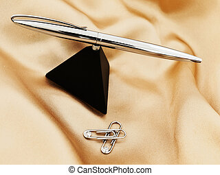ball pen - shiny ball pen and clips over the gold textile ...