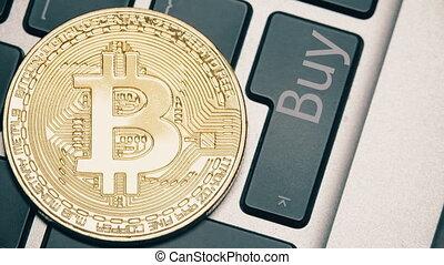 Shiny bitcoin on the laptop keyboard