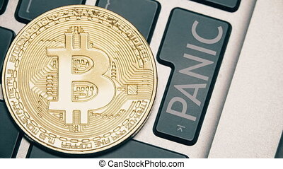 Shiny bitcoin on the computer keyboard and the PANIC button...