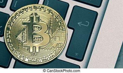 Shiny bitcoin on the computer keyboard getting dark - Shiny...