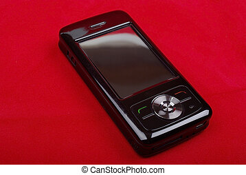 Shiny black PDA phone isolated on red background.