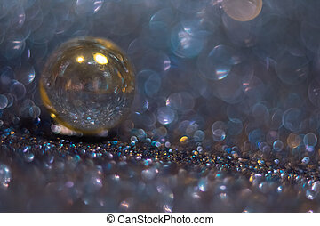 Shiny blue bokeh background with a yellow glass bead.