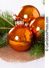 Shiny bright copper colored Christmas balls nestling in a...