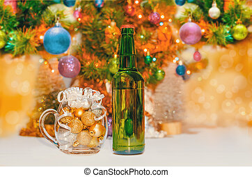 shiny christmas balls in a beer glass next to a green bottle and a decorated new year tree