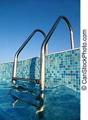 shiny chrome ladder into pool, blue sky, blue water, blue...