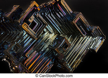 Shiny colorful mineral bismuth on a dark background -...
