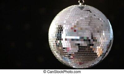 Shiny disco ball revolving on black background