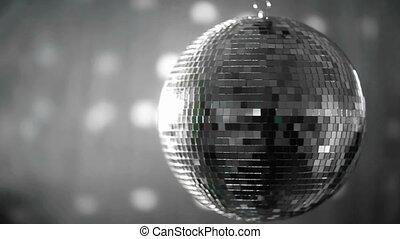 Shiny disco ball revolving on grey background