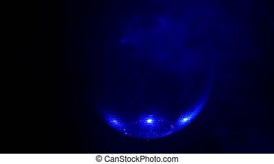 Shiny disco ball rotating around on smoke black background ....