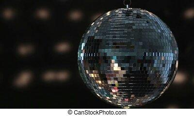 Shiny disco ball spinning around on black background