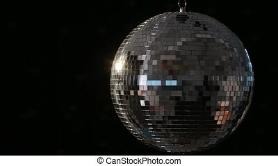 Shiny disco ball spinning on black background