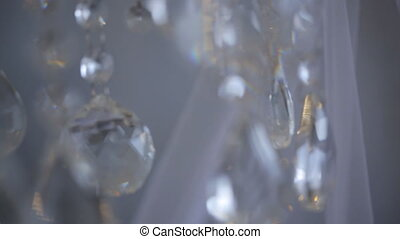 Shiny drops of sparkling crystals hang in air in white...