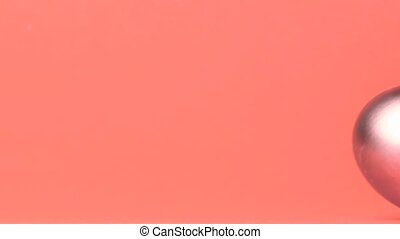 Shiny egg rolling across pink surface in slow motion